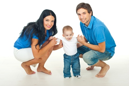 Parents helping their baby to make forst steps and smiling together