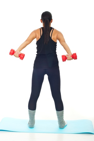 Rear view of women lifting barbell against white background photo