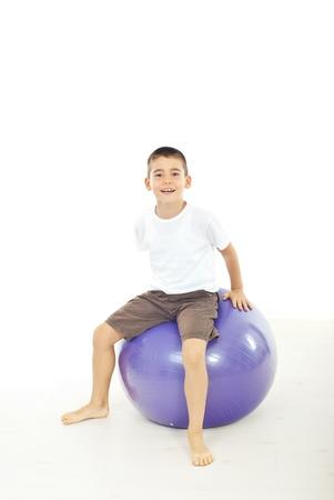 large ball: Boy sitting on big balli against white background