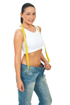 Slim young woman holding centimeter and  wearing big jeans isolated on white background photo