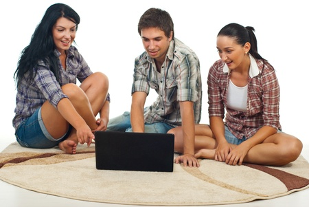 Happy friends sitting on carpet and being amazed about laptop screen over white background photo