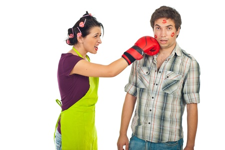 lovers quarrel: Crazy wife having conflict with surprised unfaithful husband and kick his face with boxing glove against white background