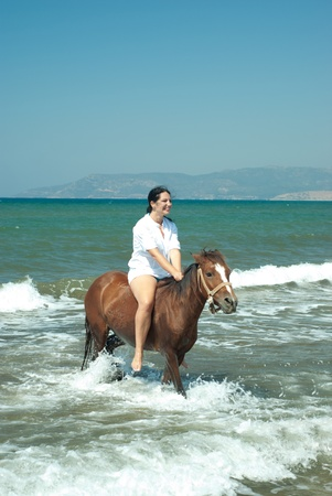 horse laugh: Laughing woman riding horse in water sea with waves