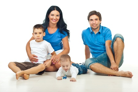 Happy family with two sons sitting on floor in their home against white background photo