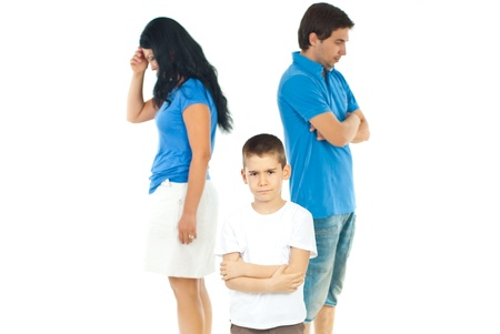 Upset boy standing with arms folded in front of parents with problems against white background Stock Photo