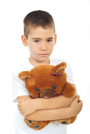 Sad boy holding teddy bear isolated on white background photo