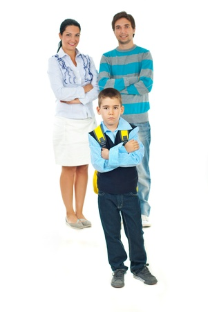 day of school: Sad schoolboy standing with arms crossed in front of smiling parents  in first day of school against white background