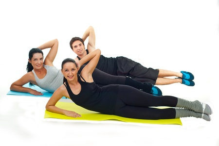 Happy team of three fitness people doing exercises on colorful mats against white background