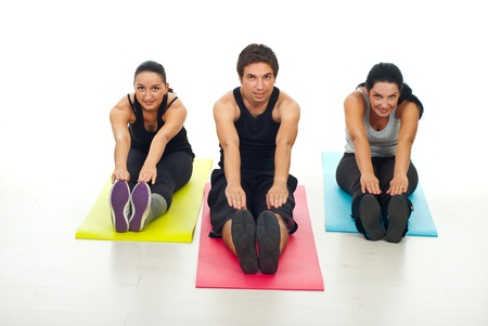 Cheerful group of fitness people stretching their bodies  and sitting on colorful mats  Stock Photo - 10657533