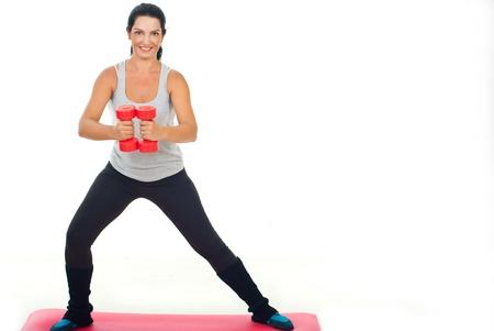 pesas: La aptitud del entrenamiento feliz mujer con mancuerna y de pie en la alfombra roja sobre fondo blanco, copia espacio para el mensaje de texto en la parte derecha de la imagen