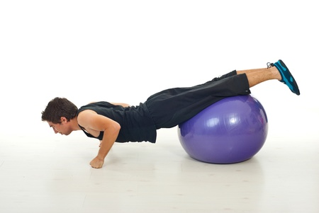 pilates man: Man doing exercises on a pilates ball