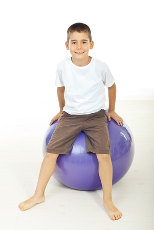 child ball: Smiling boy sitting on pilates ball barefoot