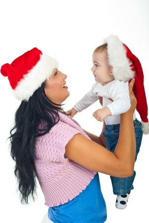 Mother holding her baby boy and wearing Santa hats at first Christmas isolated on white background photo