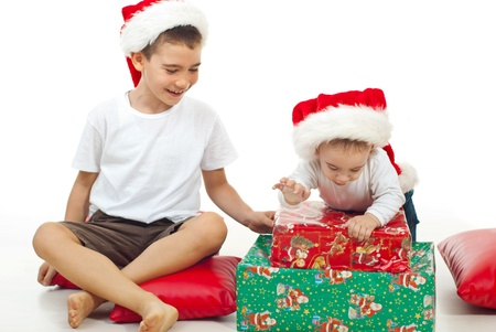 Big brother laughing about his little brother who want to open a Christmas gift  photo