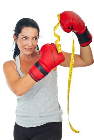 kick boxer: Woman kicking centimeter with boxing gloves,concept of fight with weights isolated on white background