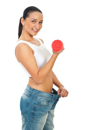 dumbell: Slim woman in large jeans working with red dumbbell isolated on white background