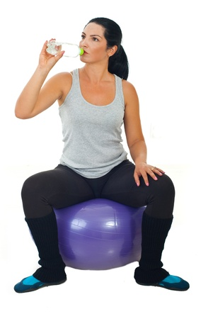 fit ball: Fitness woman sitting on pilates ball and drinking water isolated on white background