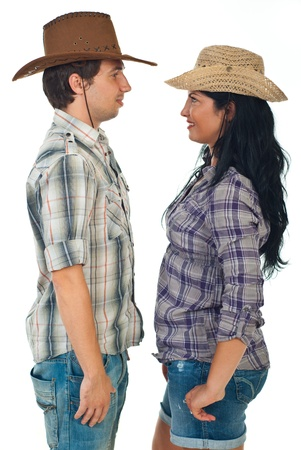 headwear: Couple wearing cowboy hats and standing face to face isolated on white background
