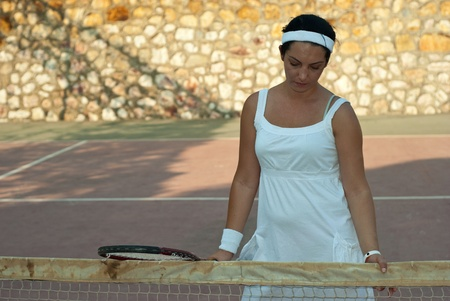 dissapointed: Dissapointed tennis player woman  holding racket and looking down
