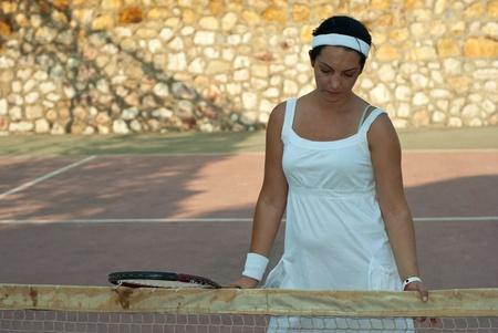 desilusion: Mujer decepcionada tenista sosteniendo la raqueta y mirando hacia abajo