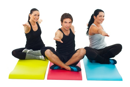 Group of three people doing yoga and sitting on colorful mats Stock Photo