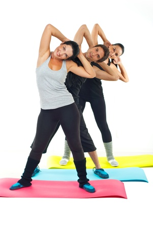 Sport people team standing on colorful mats and doing fitness exercises together Stock Photo