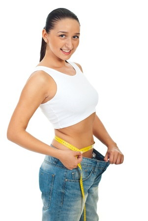 Happy slim woman in large jeans measuring her waist with centimeter isolated on white background photo