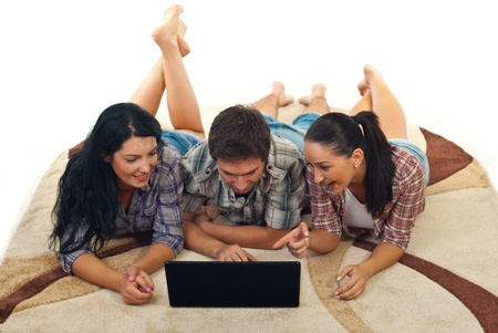 Cheerful friends lying on carpet and having fun using laptop Stock Photo - 10780232