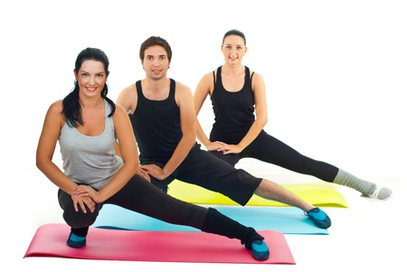 wellness background: Healthy group of three people doing fitness exercises on colorful mats Stock Photo