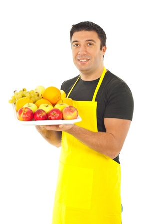 Greengrocer with yellow apron holding fruits on plateau isolated on white background photo
