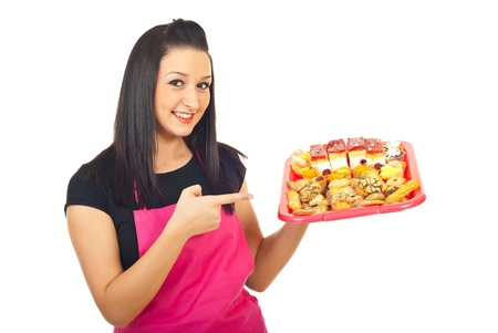 selling points: Smiling beauty confectioner woman pointing to different cakes on plateau isolated onw hite background
