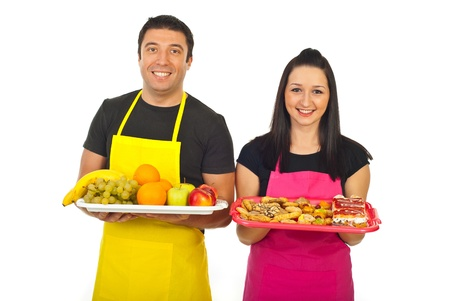 Greengrocer man and confectioner woman showing their fresh products in a market place isolated on white background photo