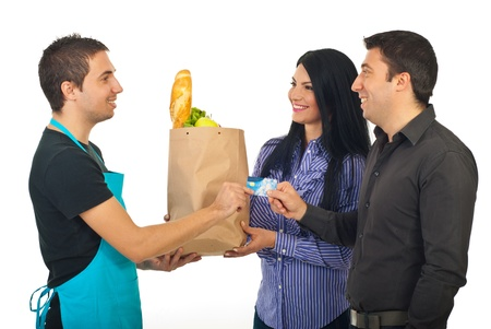 Happy couple paying by credit card their food at grocery to a salesperson man in blue apron isolated on white background photo