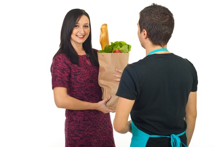 woman holding bag: Happy woman holding bag with food and talking with market worker at grocery isolated on white background