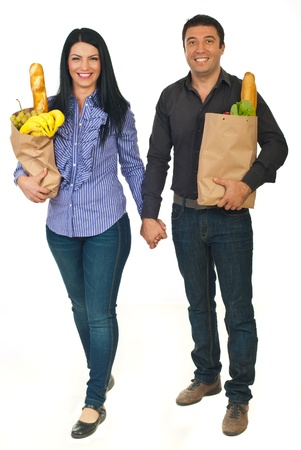 Full length of cheerful couple holding hands and carrying bags with food isolated on white background photo