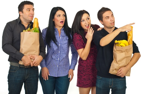 Surprised group of people friends looking away and holding paper bags with food isolated on white background photo