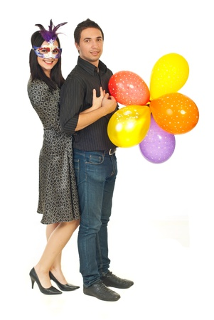 Happy young couple holding balloons at party isolated on white background photo