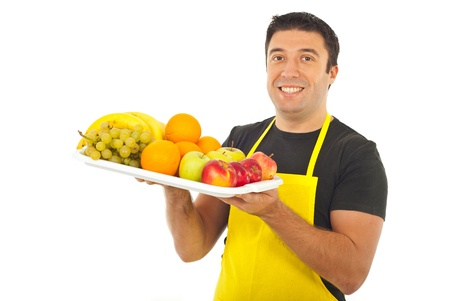 Happy market worker with yellow apron holding fruits isolated on white background photo