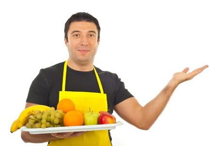greengrocer: Sonriendo meseta de la celebraci�n de verduler�a con las frutas y hacer la presentaci�n a la parte derecha de la imagen sobre fondo blanco