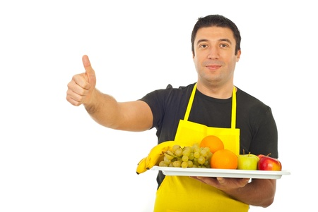 Successful fruiterer worker holding fruits and giving thumbs up isolated on white background photo