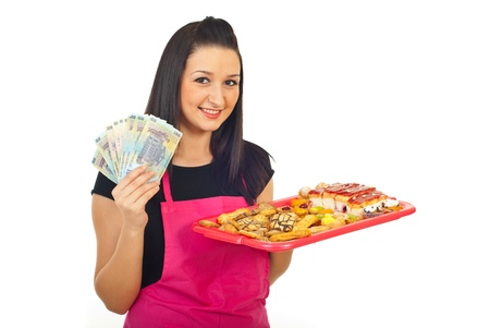 Confectioner woman holding cakes and money banknotes isolated on white background photo