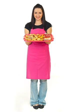 Full length of confectioner woman in pink apron holding cakes isolated on white background photo