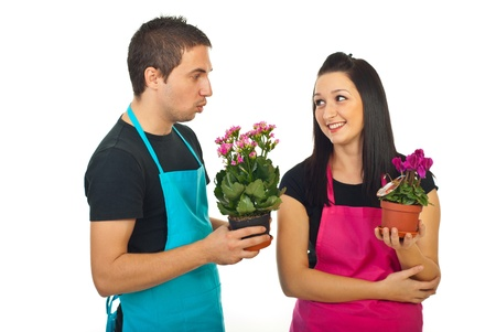 Young florists colleagues having conversation at work and holding pots with flowers isolated on white background photo