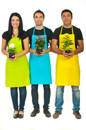 Full length of three florists team holding flowers in pots isolated on white background photo