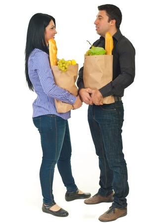 Full length of couple holding shopping paper with food and talking together isolated on hwite background photo