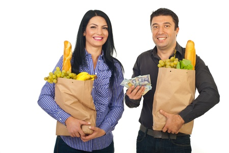 Happy couple carrying shopping paper bags with food and showing money banknotes  isolated on white background photo