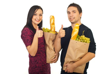 Successful couple shopping food and giving thumbs up isolated on white background photo