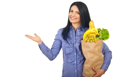 Happy woman holding shopping paper bag with groceries and showing with empty palm to left part of image isolated on white background photo