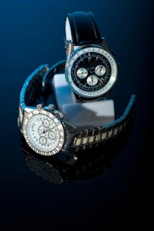 cronógrafo: Dos relojes elegantes para womans y del hombre sobre fondo negro con luz azul