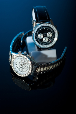 Twee elegante horloges voor womans en bemant op zwarte achtergrond met blauw licht